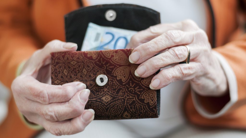 Senior women looks in her purse with Euro banknotes.