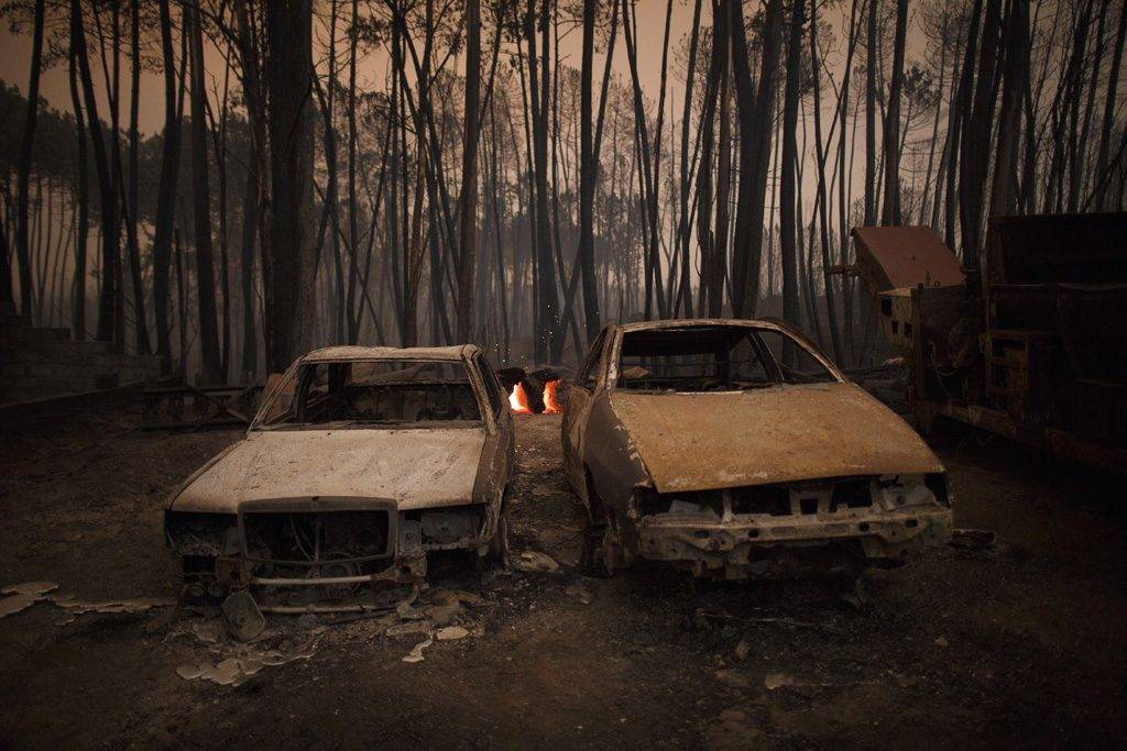 LEIRIA, PORTUGAL - JUNE 18:  Burned cars stand next to a forest after a wildfire took dozens of lives on June 18, 2017 near Castanheira de Pera, in Leiria district, Portugal. On Saturday night, a forest fire became uncontrollable in the Leiria district, killing at least 62 people and leaving many injured. Some of the victims died inside their cars as they tried to flee the area.  (Photo by Pablo Blazquez Dominguez/Getty Images)