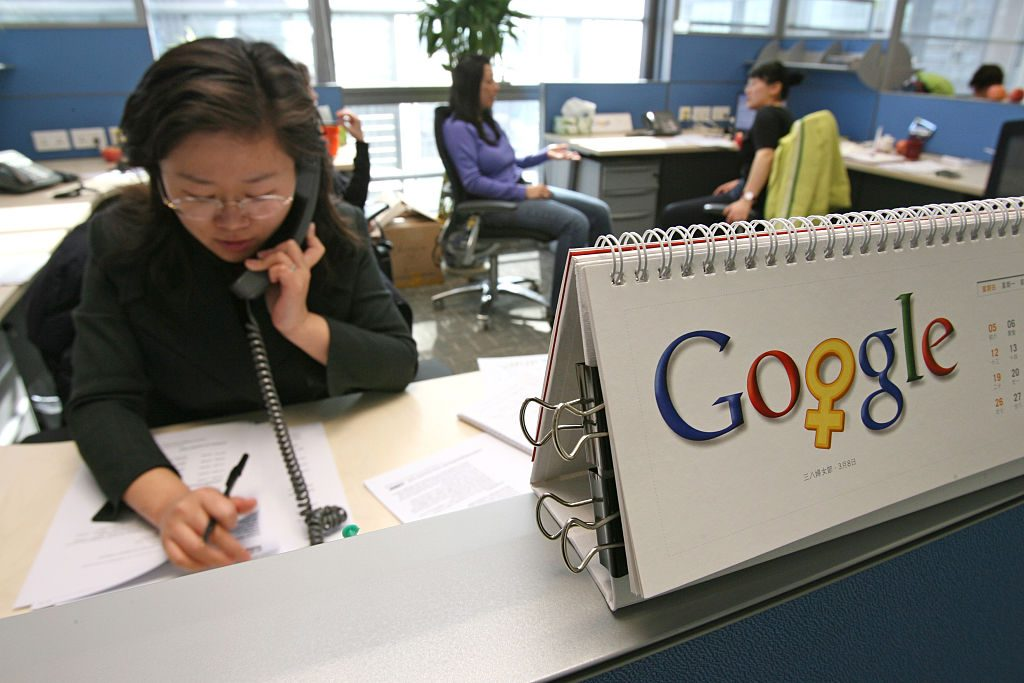 BEIJING, CHINA - March 2: A Google employee makes a phone call by a calendar that features the company's logo changed a little for the month of March in honor of Woman's day (March 8), in their offices on March 2, 2006 in Beijing, China. (Photo by Servais Mont/Getty Images)