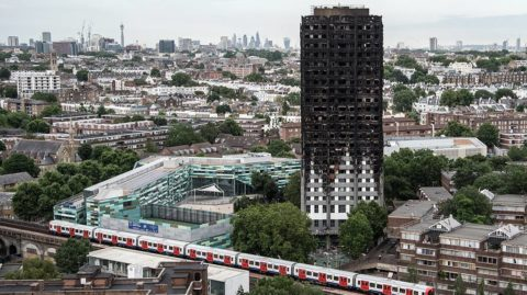 LONDON, ENGLAND - JUNE 26:  A tube train passes the remains of Grenfell Tower, seen from a neighbouring tower block on June 26, 2017 in London, England. 79 people have been confirmed dead and dozens still missing after the 24 storey residential Grenfell Tower block was engulfed in flames in the early hours of June 14, 2017.  (Photo by Carl Court/Getty Images)