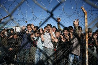Immigrant minors peer out through the fence of an immigrant detention center in the village of Filakio, on the Greek-Turkish border, upon the arrival there of the Frontex Rapid Border Intervention Teams (RABITs) and EU officials on November 5, 2010. Border guards from 26 nations began arriving on November 2 in northeastern Greece to help curb a wave of illegal immigrants crossing over from Turkey, European border agency Frontex said. Coordinated by Greek police, some 170 guards will be on hand and until the end of December to monitor borders and scout for illegal immigrants, Frontex spokesman Michal Parzyszek said. AFP PHOTO /Sakis Mitrolidis