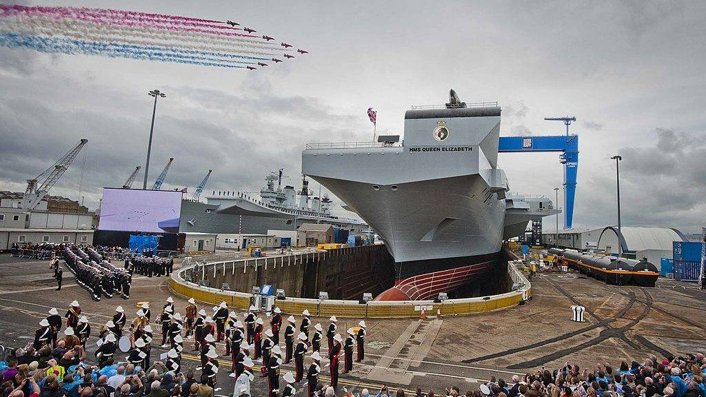 Rosyth, SCOTLAND - JULY 03: Red Arrows mark the naming of Royal Navy's new aircraft carrier HMS Queen Elizabeth by Queen Elizabeth II  on July 4, 2014 in Rosyth, Scotland.  HMS Queen Elizabeth is the largest warship ever built in the UK weighing 65,000-tonnes, six shipyards around the UK have been involved in building various parts of the carrier. The ship is capable of carrying up to forty aircraft, is scheduled to be launched later this summer, and to commission in early 2017, with full operational capability from 2020. (Photo by Chris Watt/Getty Images)