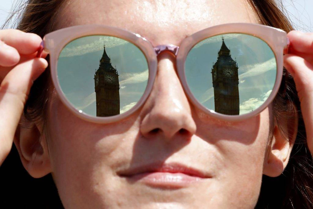 A tourist has the Elizabeth Tower, commonly referred to as Big Ben reflected in her mirror lenses as the sun shines in central London on June 16, 2017. Britain and the European Union will start Brexit negotiations on Monday, while Prime Minister Theresa May nears a deal to prop up her minority government following her election fiasco. / AFP PHOTO / Tolga AKMEN