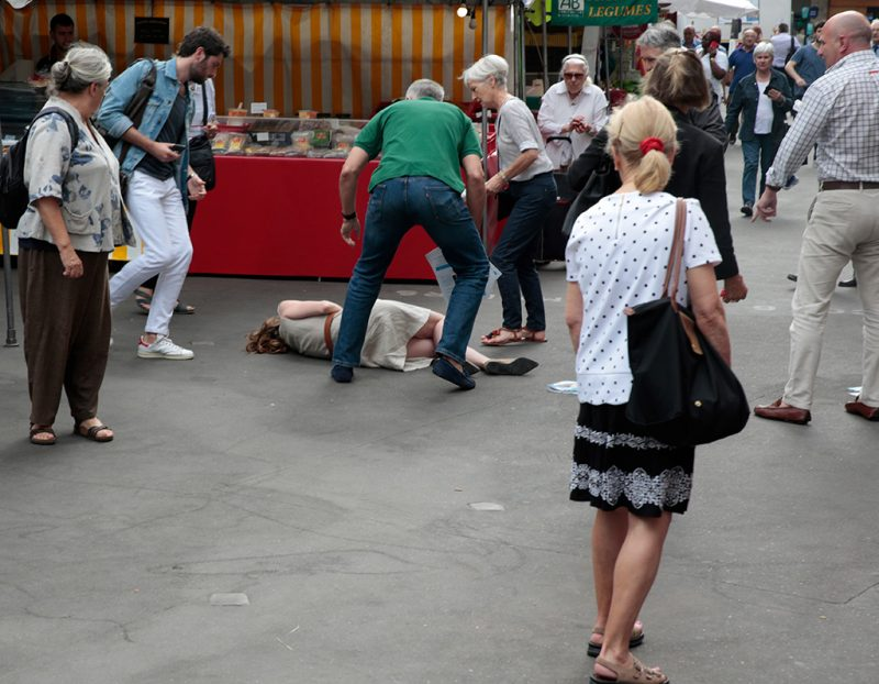 Bystanders give assistance after Les Republicains (LR) party candidate Nathalie Kosciusko-Morizet collapsed following an altercation with a man (R) while campaigning in the 5th arrondissement in Paris on June 15, 2017, ahead of the second round of the French legislative election. / AFP PHOTO / GEOFFROY VAN DER HASSELT