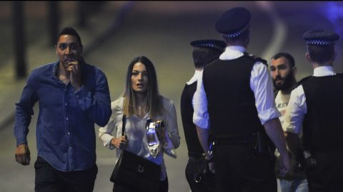 """Members of the public leave the scene of a terror attack on London Bridge in central London on June 3, 2017. Armed police opened fire during what they described as a """"terrorist"""" attack in central London Saturday after reports of stabbings and a van ploughing into pedestrians just days ahead of a general election. / AFP PHOTO / DANIEL SORABJI"""