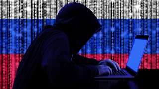 Hacker in a dark hoody sitting in front of a notebook with digital russian flag and binary streams background cybersecurity concept