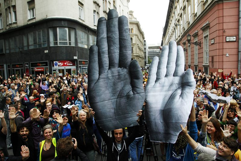 """Budapest, 2014. szeptember 13.A kormány civil szervezetekkel kapcsolatos politikája és a Norvég Civil Támogatási Alapot koordináló civil szervezetekkel szembeni rendőri fellépés elleni tiltakozók Budapesten, a Városház téren 2014. szeptember 13-án. A résztvevők kartonpapírból formázott nyitott tenyereket tartanak a magasba, annak szimbólumaként, hogy megálljt parancsoljanak a civil szervezetek elleni """"kormányzati támadásoknak"""".MTI Fotó: Járdány Bence"""