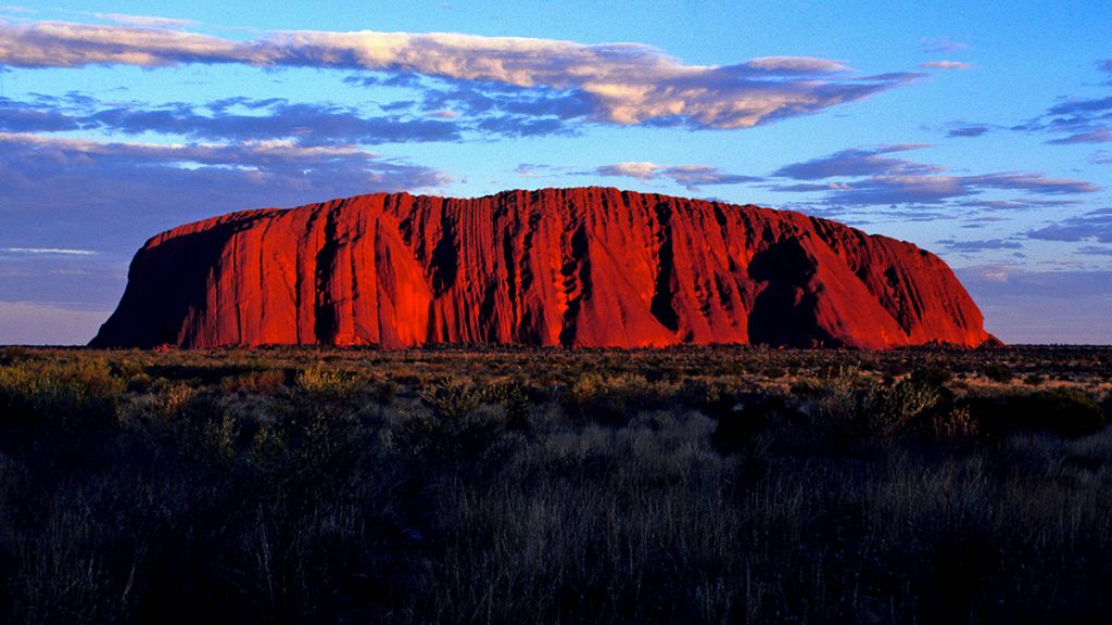 AUSTRALIA. NORTHERN TERRITORY. ULURU-KATA TJUTA NATIONAL PARK. SUNSET ON AYERS ROCK LISTED AS NATURAL SITE BY UNESCO WORLD HERITAGE