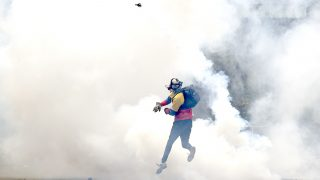 """An opposition activist throws back tear gas to the police, as clashes erupt during a protest against President Nicolas Maduro, in Caracas on May 8, 2017.Venezuela's opposition mobilized Monday in fresh street protests against President Nicolas Maduro's efforts to reform the constitution in a deadly political crisis. Supporters of the opposition Democratic Unity Roundtable (MUD) gathered in eastern Caracas to march to the education ministry under the slogan """"No to the dictatorship."""" / AFP PHOTO / JUAN BARRETO"""