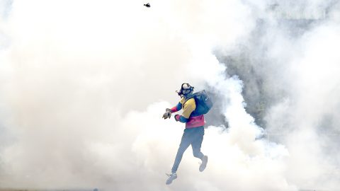 An opposition activist throws back tear gas to the police, as clashes erupt during a protest against President Nicolas Maduro, in Caracas on May 8, 2017.