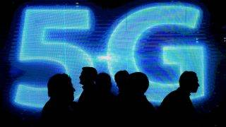 Visitors walk past a 5G logo during the Mobile World Congress on the third day of the MWC in Barcelona, on March 1, 2017. 