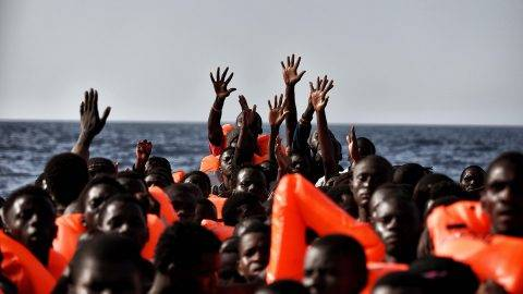 Migrants wait to be rescued as they drift in the Mediterranean Sea some 20 nautical miles north off the coast of Libya on October 3, 2016.  Italy coordinated the rescue of more than 5,600 migrants off Libya, three years to the day after 366 people died in a sinking that first alerted the world to the Mediterranean migrant crisis.   / AFP PHOTO / ARIS MESSINIS