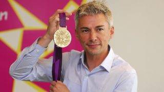 - EDITORS NOTE - RESTRICTED TO EDITORIAL USE - MANDATORY CREDIT AFP PHOTO / LOCOG / HO - NO MARKETING - NO ADVERTISING CAMPAIGNS - DISTRIBUTED AS A SERVICE TO CLIENT - A handout image obtained from the London 2012 organising committee (LOCOG) on July 27, 2011 shows British triple jump Olympic gold medallist Jonathan Edwards posing with the London 2012 Olympic gold medal. The Olympic medals' circular form is a metaphor for the world. The front of the medal always depicts the same imagery at the summer Games, the Greek Goddess of Victory, Nike, stepping out of the depiction of the Parthenon to arrive in the host city. The design for the reverse of the London 2012 Olympic medals contains five main symbolic elements: the dished background suggests a bowl similar to the design of an amphitheatre, the core emblem is an architectural expression, a metaphor for the modern City, the grid brings both a pulling together and sense of outreach on the design - an image of radiating energy that represents the athletes' achievements and effort, the River Thames is a symbol for London and the square is the final balancing motif of the design, opposing the overall circularity of the design and emphasising its focus on the centre and reinforcing the sense of 'place' as in a map inset. AFP PHOTO / LOCOG/ HO  ATTENTION - EMBARGO, RELEASABLE Wednesday July 27, 2011 at 1830 GMT - THIS RESTRICTION APPLIES TO ALL MEDIA INCLUDING WEBSITES   ---- EDITORS NOTE ---- RESTRICTED TO EDITORIAL USE - MANDATORY CREDIT *AFP PHOTO / LOCOG/ HO* - NO MARKETING NO ADVERTISING CAMPAIGNS - DISTRIBUTED AS A SERVICE TO CLIENTS / AFP PHOTO / LOCOG / -