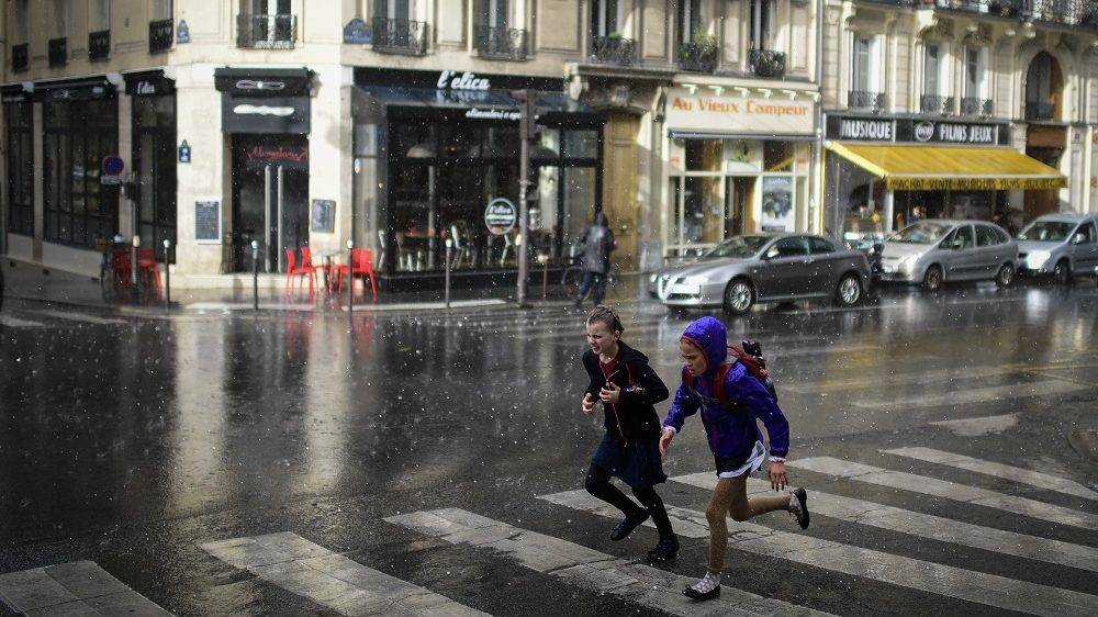 Two young children run across a road towards shelter as heavy rain falls in Paris on June 6, 2017. / AFP PHOTO / Martin BUREAU