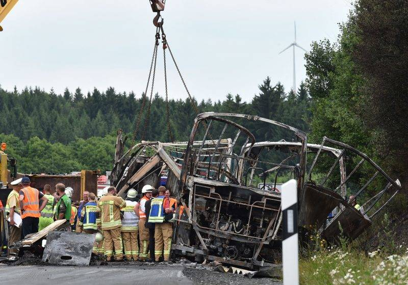 Members of the fire brigade work on the scene where a tour bus burst into flames following a collision with a trailer truck on the highway A9 near Münchberg, southern Germany, on July 3, 2017, where up to 17 people are feared dead  / AFP PHOTO / Christof Stache