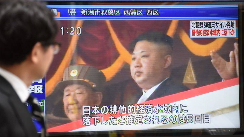 """A pedestrian walks past a screen in Tokyo on July 4, 2017 broadcasting file news footage of North Korean leader Kim Jong-Un, after a ballistic missile was launched by North Korea earlier in the day. North Korea launched the ballistic missile on July 4 as the US prepared to mark its Independence Day, triggering a Twitter outburst from President Donald Trump who urged China to """"end this nonsense once and for all"""". / AFP PHOTO / KAZUHIRO NOGI"""