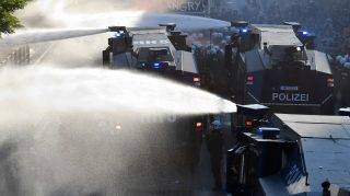 """Riot police use water cannon during the """"Welcome to Hell"""" rally against the G20 summit in Hamburg, northern Germany on July 6, 2017.  Leaders of the world's top economies will gather from July 7 to 8, 2017 in Germany for likely the stormiest G20 summit in years, with disagreements ranging from wars to climate change and global trade. / AFP PHOTO / John MACDOUGALL"""