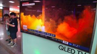 People use their mobile phones next to a television screen showing a video footage of North Korea's latest test launch of an intercontinental ballistic missile (ICBM), at a railway station in Seoul on July 29, 2017. North Korean leader Kim Jong-Un said on July 29 the country's second ICBM test demonstrated the ability to strike any target in the United States, in a direct challenge to President Donald Trump who had issued dire warnings over its missile program. / AFP PHOTO / JUNG Yeon-Je
