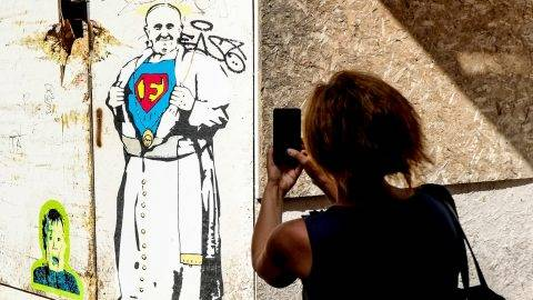 A woman takes a picture of street art depicting Pope Francis by artist TvBoy on July 2, 2017, near Piazza Navona in central Rome.   / AFP PHOTO / ANDREAS SOLARO / RESTRICTED TO EDITORIAL USE - MANDATORY MENTION OF THE ARTIST UPON PUBLICATION - TO ILLUSTRATE THE EVENT AS SPECIFIED IN THE CAPTION