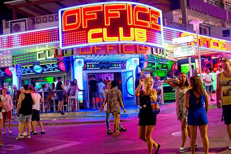"""MALLORCA, SPAIN - JULY 12:  Tourists are seen enjoying the atmosphere of Punta Ballena Street, also known as """"the strip"""" on July 12, 2014 in Mallorca, Spain. Magaluf is one of the Britain's favorite holiday destinations popular because of it's beautiful beaches, bars, and active nightlife.  (Photo by David Ramos/Getty Images)"""