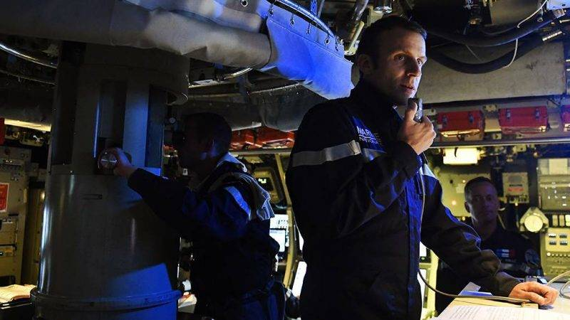 """In this photograph taken at sea on July 4, 2017, French president Emmanuel Macron speaks to the Captain and crew of the submarine """"Le Terrible"""" from the operations centre of the vessel.  / AFP PHOTO / POOL / Fred TANNEAU"""