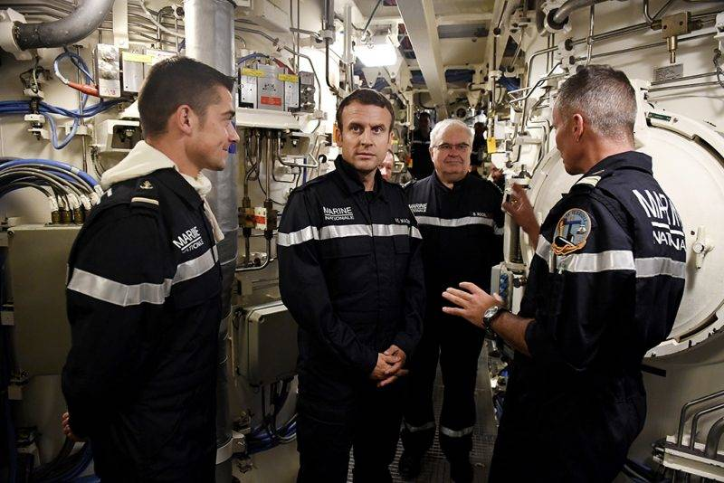 """In this photograph taken at sea on July 4, 2017, French president Emmanuel Macron (C) looks on as he stands with Captain Jerome Halle (R), commanding officer of SSBN submarine """"Le Terrible"""" and Chief of the Special General Staff Admiral Bernard Rogel (2R) and crew during a visit to the missile room of the vessel.   / AFP PHOTO / POOL / Fred TANNEAU"""