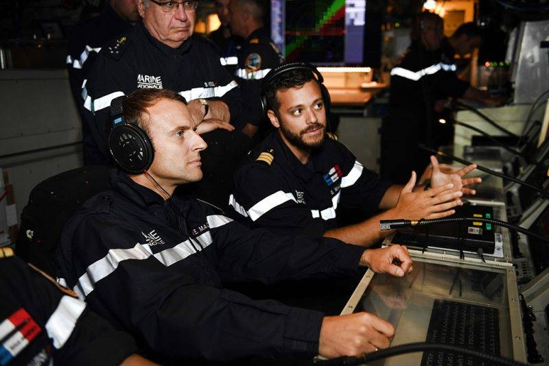 """In this photograph taken at sea on July 4, 2017, French president Emmanuel Macron (L) and Chief of the Special General Staff Admiral Bernard Rogel (TOP) listen as an acoustic expert (R) of the submarine """"Le Terrible"""", explains how a submarine monitors its surroundings, in the operations centre of the vessel.  / AFP PHOTO / POOL / Fred TANNEAU"""