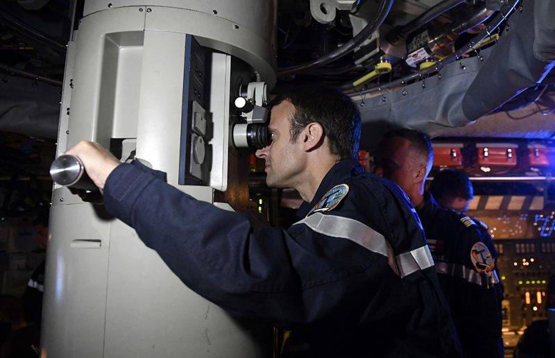 """In this photograph taken at sea on July 4, 2017, French president Emmanuel Macron (C) looks through the periscope of submarine """"Le Terrible"""" during a visit to the vessel.   / AFP PHOTO / POOL / Fred TANNEAU"""