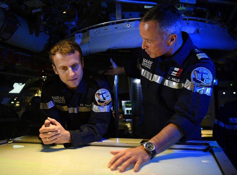 """In this photograph taken at sea on July 4, 2017, French president Emmanuel Macron (L) listens as Captain Jerome Halle, commanding officer of the submarine """"Le Terrible"""" speaks in the operations centre of the vessel.  / AFP PHOTO / POOL / Fred TANNEAU"""