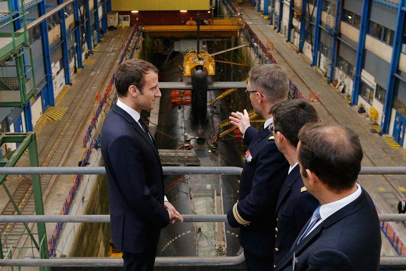 French President Emmanuel Macron (L) listens to explanations in front of a nuclear submarine, during his visit to the Ile Longue Defence unit, a submarine navy base, in Crozon, near Brest, western France, on July 4, 2017.  / AFP PHOTO / POOL / STEPHANE MAHE