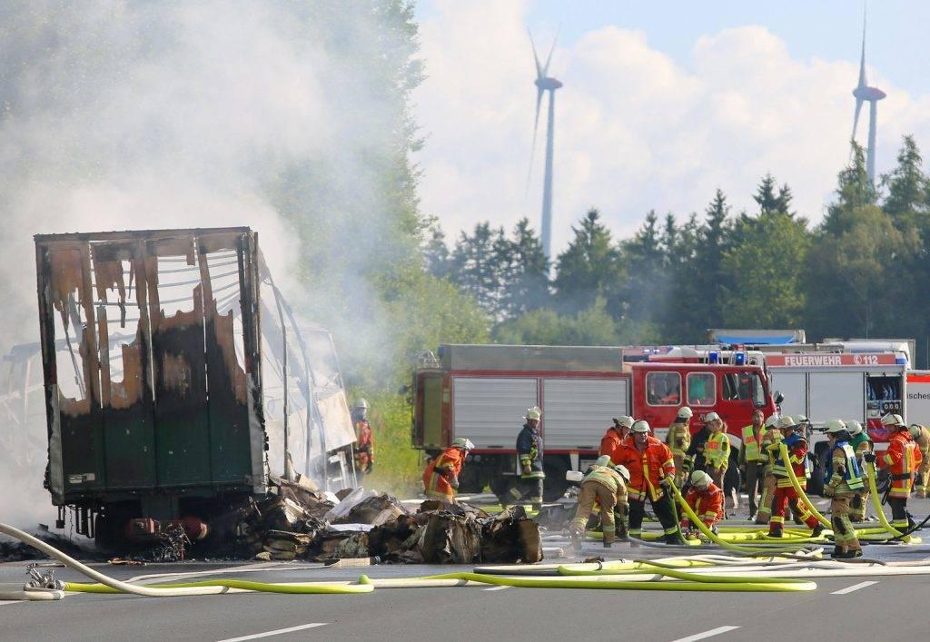 Münchberg, 2017. június 3. Autóbusz kiégett roncsa mellett mentõk az A9-es autópályán 2017. július 3-án, miután a jármû kamionba rohant, majd kigyulladt a bajorországi Münchberg közelében. Tizenhét ember sorsa ismeretlen, harmincegy megsérült. (MTI/EPA/News5/Stephan Fricke)