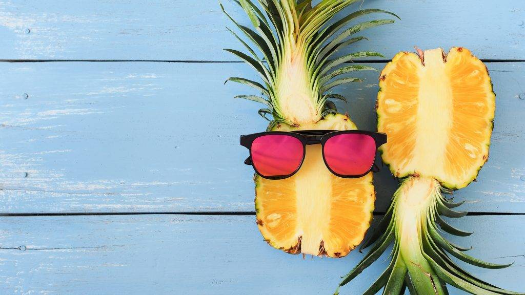Ripe fresh pineapple and sunglasses on blue wooden table for summer fruit concept with copy space.