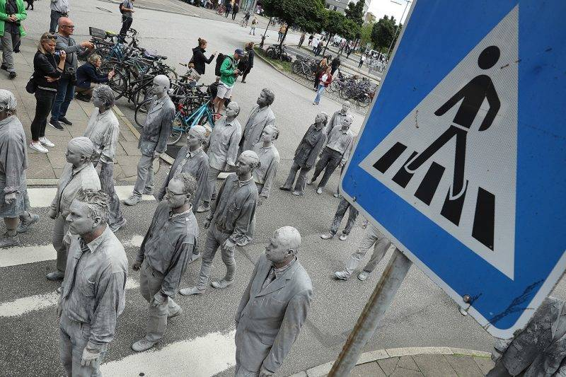HAMBURG, GERMANY - JULY 05:  Performance artists covered in clay to look like zombies walk over a crosswalk trance-like through the city center on July 5, 2017 in Hamburg, Germany. In a two-hour show hundreds of actors took part in a creative public appeal for more humanity and self-responsibility ahead of the upcoming G20 summit. The G20 economic summit takes place in Hamburg July 7-8.  (Photo by Sean Gallup/Getty Images)