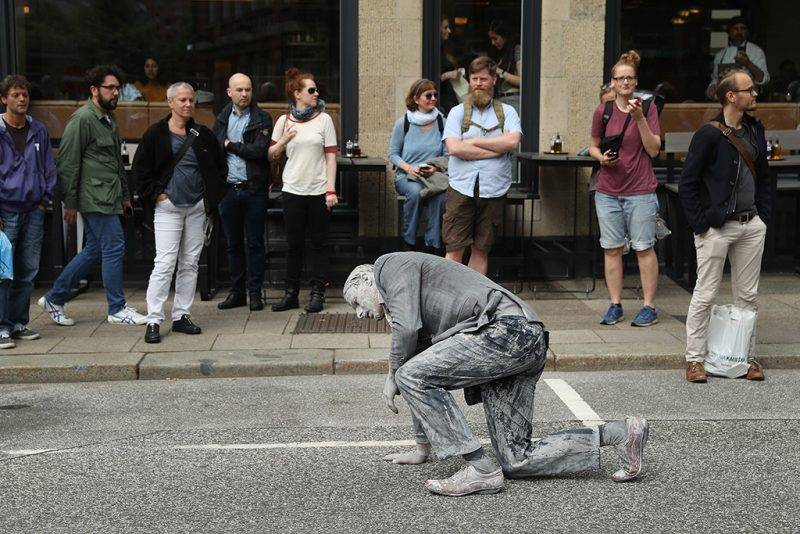 HAMBURG, GERMANY - JULY 05:  A performance artist covered in clay to look like a zombie walks and stumbles trance-like through the city center on July 5, 2017 in Hamburg, Germany. In a two-hour show hundreds of actors took part in a creative public appeal for more humanity and self-responsibility ahead of the upcoming G20 summit. The G20 economic summit takes place in Hamburg July 7-8.  (Photo by Sean Gallup/Getty Images)