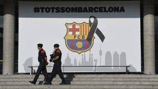 """Armed Catalan policemen, known as Mosso d'Esquadra pass by the FC Barcelona logo with a black ribbon and a message reading """"We are all Barcelona"""" before the Spanish league footbal match FC Barcelona vs Real Betis at the Camp Nou stadium in Barcelona on August 20, 2017.Security barriers were put up at the entrances of the Camp Nou to stop vehicles after a deadly jihadist attack three days ago. An outcry has erupted on social media and in the press about the absence of bollards -- short, concrete posts to stop vehicles from driving onto sidewalks, with some people even demanding the  mayor's resignation for ignoring police recommendations for such preventive barriers. Drivers have ploughed on August 17, 2017 into pedestrians in two quick-succession, separate attacks in Barcelona and another popular Spanish seaside city, leaving 14 people dead and injuring more than 100 others / AFP PHOTO / LLUIS GENE"""