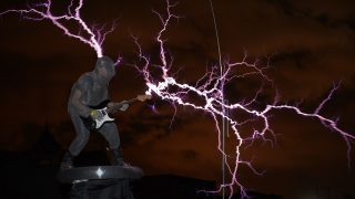 """The guitarist of the band """"Lightningfan"""" Wang Hongbin (L) creates lightning with a Tesla Coil in their village outside of Fuzhou in China's Fujian province on June 24, 2013. The Tesla Coil invented by Nikola Tesla in 1891 is a transformer that produces vast amounts of voltage at high frequencies that creates long bolts of electricity like lightening. Inventor and founding member of the band Wang Zengxiang, an electrical engineer made his first Tesla Coil in 2007 and afterwards formed his 10 member band who, whilst wearing ferroalloy metal suits play guitars, violins and drums with bolts of lightening crackling from them and their instruments to the beat. AFP PHOTO/Peter PARKS / AFP PHOTO / PETER PARKS"""
