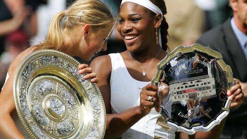 Maria Sharapova of Russia and Serena Williams of US hold their trophies after their ladies final match at the 118th Wimbledon Tennis Championships in Wimbledon, London 03 July, 2004. Sharapova won 6-1, 6-4.    AFP PHOTO/ODD ANDERSEN / AFP PHOTO / ODD ANDERSEN
