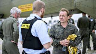 "Peter Madsen (R), builder and captain of the private submarine ""UC3 Nautilus"" talks to a police officer in Dragoer Harbor south of Copenhagen on Friday, August 11, 2017, following a major rescue operation after the submarine sank in the sea outside Copenhagen Harbor. A swedish woman supposed to be on board the submarine is still missing.  / AFP PHOTO / Scanpix Denmark / Bax Lindhardt / Denmark OUT"