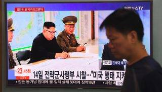 A man walks past a television news screen showing North Korean leader Kim Jong-Un receiving a briefing, at a railway station in Seoul on August 15, 2017. North Korean leader Kim Jong-Un has been briefed on a plan to fire missiles near Guam but hinted that he would hold off on the launch, Pyongyang's state media said on August 15. / AFP PHOTO / JUNG Yeon-Je