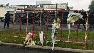 """Police officers patrol next to a makeshift memorial in front of the scene of a car crash into a pizza restaurant on August 15, 2017 in Sept-Sorts, 55km east of Paris, resulting in the death of a 13-year-old girl and seriously injuring 13. Investigators said the young driver had tried to commit suicide and the incident was not terror-related. The man, who was arrested, said """"he had tried to kill himself yesterday (August 13) without success and decided to try again this way,"""" a source close to the inquiry said. / AFP PHOTO / Sarah BRETHES"""