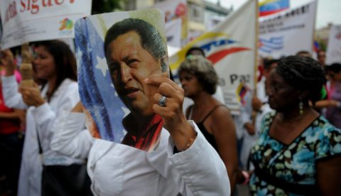 """A woman holds a picture of the late Venezuelan President Hugo Chavez during a march in solidarity with Venezuelan President Nicolas Maduro, on August 25, 2017 in Havana. On the eve, Maduro -who has been facing months of deadly mass protests by opponents demanding elections to replace him- warned the armed forces against """"fissures"""" in their ranks, ahead of war games seen as a show of strength after US President Donald Trump's threat of military action. / AFP PHOTO / YAMIL LAGE"""