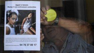 The owner of a bar attaches an appeal for witnesses poster issued by the Gendarmerie of Pont-de-Beauvoisin for Maelys, a 9-year-old girl, who disappeared during a wedding party on August 26 overnight in Pont-de-Beauvoisin, eastern France, on August 28, 2017. An investigation into kidnapping has been opened on the morning of August 28 while the search was continuing for 9-year-old Maelys, who was seen for the last time at 3am on August 27, 2017 as she attended a wedding party with her parents and relatives. / AFP PHOTO / PHILIPPE DESMAZES