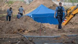 A policeman walks past a blue tent covering a British World War II bomb that was found during construction works on August 30, 2017 in Frankfurt am Main, western Germany. The disposal of the bomb that is planned for Sunday, September 3, 2017 requires the evacuation of around 70,000 people. / AFP PHOTO / dpa / Boris Roessler / Germany OUT