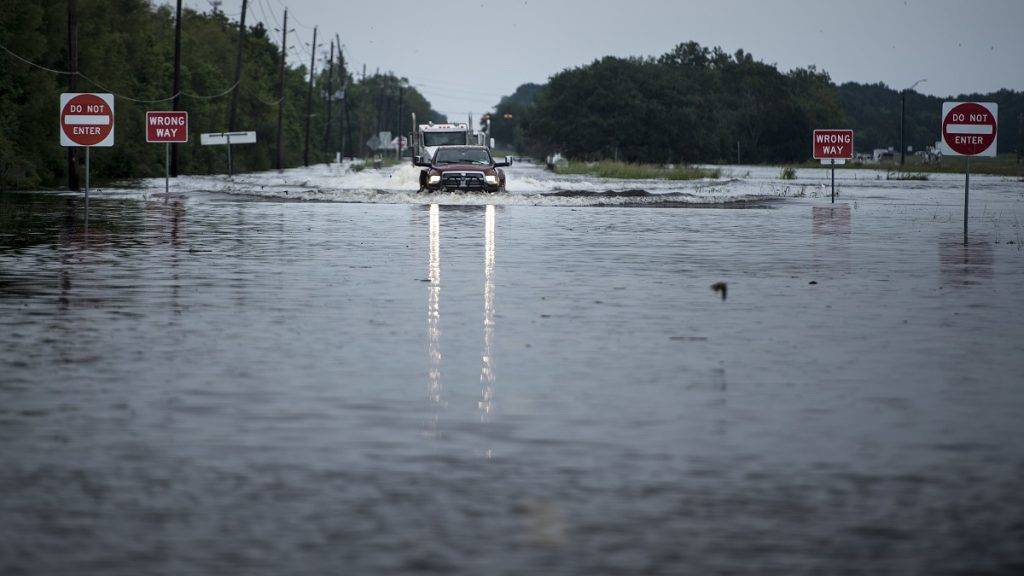 Trucks make their way through flood waters on a main road leading to the Arkema Inc. chemical plant that was in crisis during the aftermath of Hurricane Harvey on August 30, 2017 in Crosby, Texas. After pouring  record rains on Texas, Tropical Storm Harvey made a second landfall Wednesday to strike Louisiana, a state that still bears deep scars from 2005's Hurricane Katrina. / AFP PHOTO / Brendan Smialowski