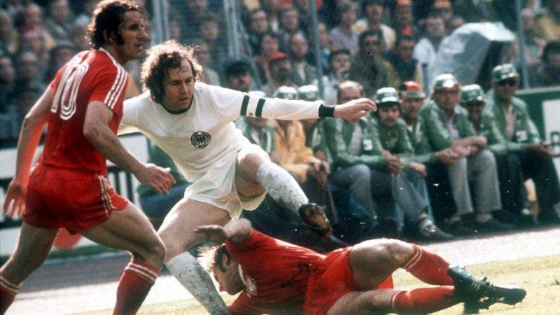 German sweeper and team captain Franz Beckenbauer in a duel with a Polish player, lying on the ground who is supported by teammate Adam Musial. The German national football team wins the last group round match 1:0 against Poland at Frankfurt's Waldstadion and thus enters the 1974 FIFA World Cup final.