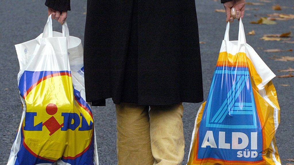 """A woman carries one plastic bag of the discounter """"Lidl"""" and one of """"Aldi"""" in Cologne on 17 November 2003. Germany's second-biggest discounter Lidl is no longer overshadowed by the industry's number one Aldi."""