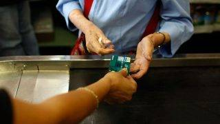 MIAMI - MAY 20:  Yera Dominguez receives a credit card from a customer for payment at Lorenzo's Italian Market on May 20, 2009 in Miami, Florida. Members of Congress today passed a bill placing new restrictions on companies that issues credit. The vote follows the Senate passage of the bill, which now heads for President Obama's promised signature. The bill will curb sudden interest rate increases and hidden fees, requiring card companies to tell customers of rate increases 45 days in advance. It will also make it harder for people aged below 21 to be issued credit cards.  (Photo by Joe Raedle/Getty Images)