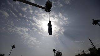 EDITORS NOTE: Graphic content / The body of Yemeni Hussein al-Saket, 22, is seen hanging after being executed by security forces for raping and murdering a four-year-old girl, in the capital Sanaa's Tahrir Square, on August 14, 2017. Yemenis gathered in the rebel-held capital to witness the putting to death of a man convicted of raping and killing a child in the second such public execution in weeks. Al-Saket, was found guilty of abducting, raping and murdering a four-year-old girl, said Rajeh Ezzedine, a judge who attended the execution.  / AFP PHOTO / Mohammed HUWAIS