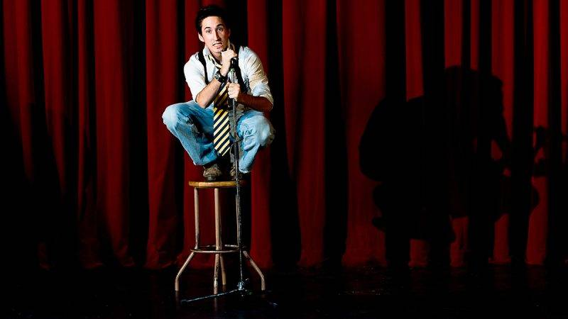 Man squatting atop stool on stage