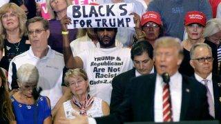 PHOENIX, AZ - AUGUST 22: A supporter of U.S. President Donald Trump holds up a sign as the president speaks to a crowd at the Phoenix Convention Center during a rally on August 22, 2017 in Phoenix, Arizona.   Ralph Freso/Getty Images/AFP